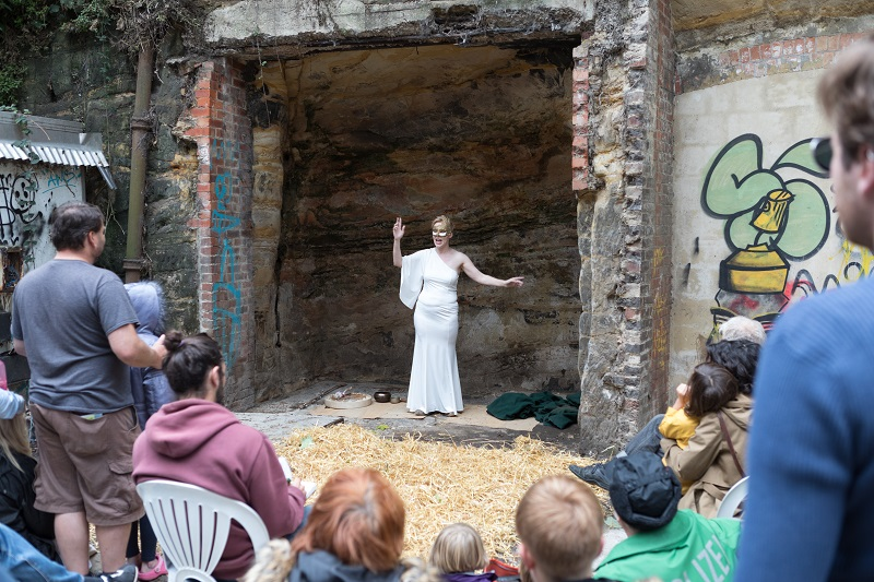 A woman wearing a white costume dress is performing inside a cave, facing outwards to audience