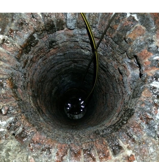 looking downwards into a dark, circular hole, cable is seen feeding into the blackness