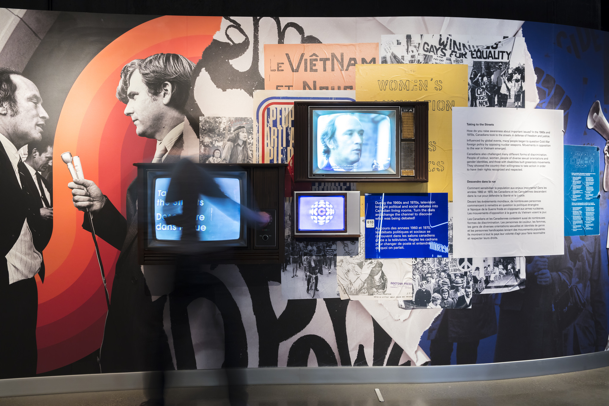 Three faces of television sets emerge from a wall covered in museum text. A blurred figure is turning one of the dials on the television.