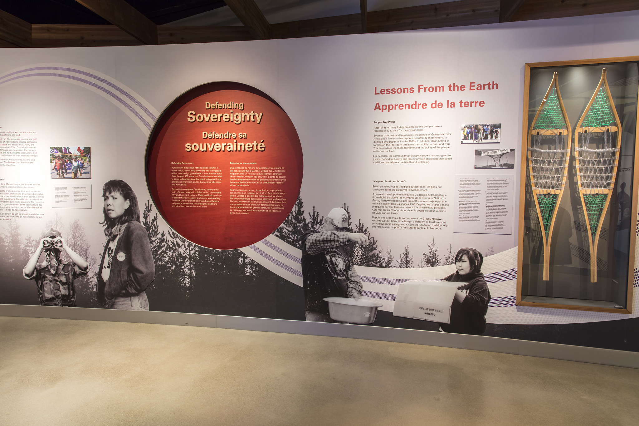 A wall with a depressed red circle in the center containing exhibition text on the left. To the right, a pair of show shoes in a glass case.